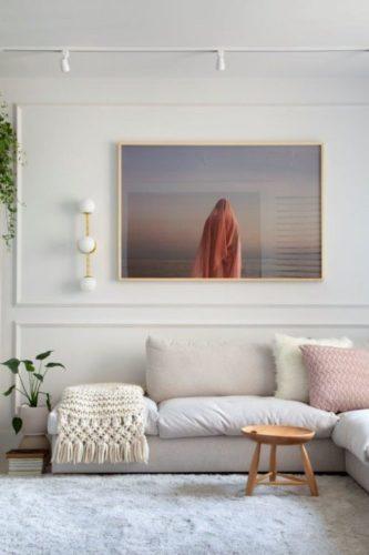 Parede com boiserie pintada da mesam cor da parede, branco e uma foto de uma mulher de costas usando burca