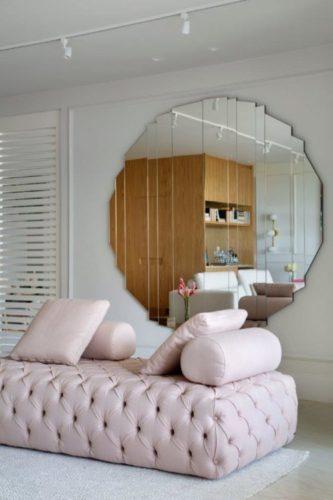 Espelho redondo na parede e em frente um recamier capitone na cor rosa