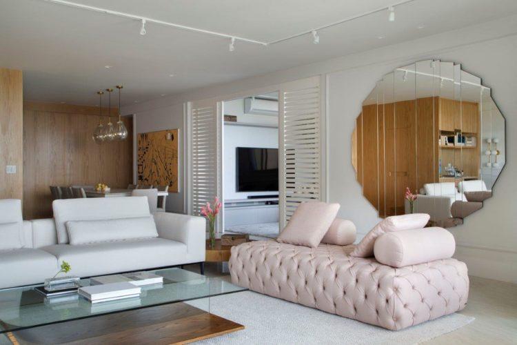 Apartamento de 300 m2 com décor contemporâneo, recamier rosa em capitone, um espelho grande redondo na parede e uma mesa de centro em vidro e madeira.