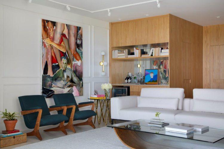 Sala com duas poltronas verdes, assinadas por Zanine Caldas; E ao fundo uma estante bar