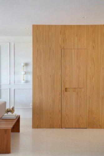 Parede revestida em madeira, acabamento Carvalho Americano, camufando a porta do lavabo