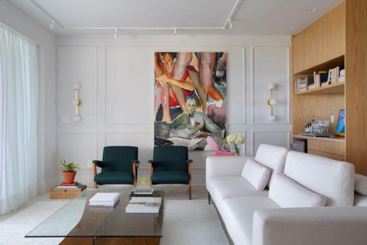 Apartamento de 300 m2 com décor contemporâneo. Sala com sofá branco, duas poltronas verdes e uma quadro colorido na parede