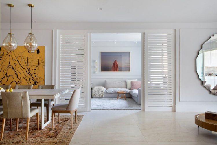 Apartamento de 300 m2 com décor contemporâneo. Sala com piso claro, portas ripdas que abrem para a sala de tv