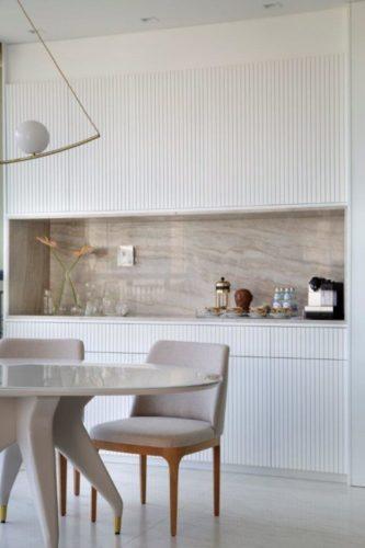 Parede de armarios com portas e ripadas em branco e um nicho de marmore no meio.