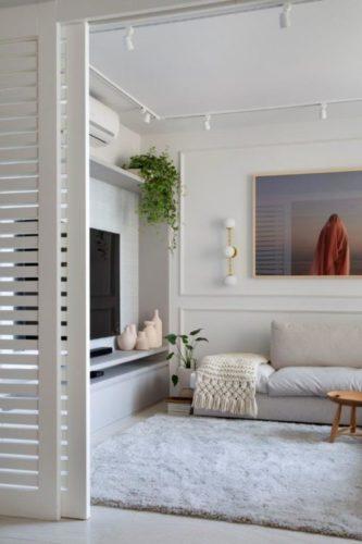 Apartamento de 300 m2 com décor contemporâneo, porta ripada para a sala da tv