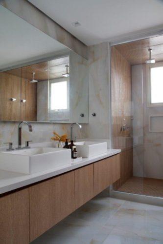 Banheiro com piso em porcelanto imitando pedra ônix, bancada branca e armaruos em madeira