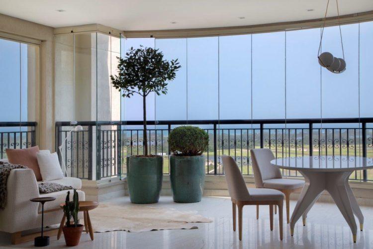 Apartamento de 300 m2 com décor contemporâneo. Varanda fechada com paineis em vidro e decoração como uma sala de estar; Sofá, mesa redonda e vasos
