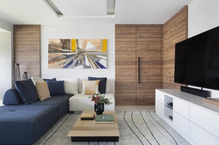 Com a saída de casa dos filhos, casal decidiu reformar o apartamento para aproveitar a nova fase da vida. Sala com sofá azul, portas e painel em madeira