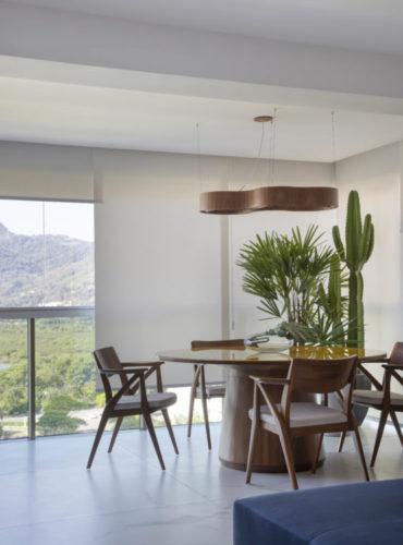 Varanda fechada com vidro, mesa redonda e plantas