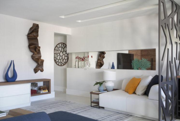 Sala com paredes brancas, um sofá recamier e em cima uma faixa de espelho