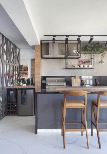 Com a saída de casa dos filhos, casal decidiu reformar o apartamento para aproveitar a nova fase da vida.Espaço gourmet no aparatemento, churrasqueira, bancada e geladeira