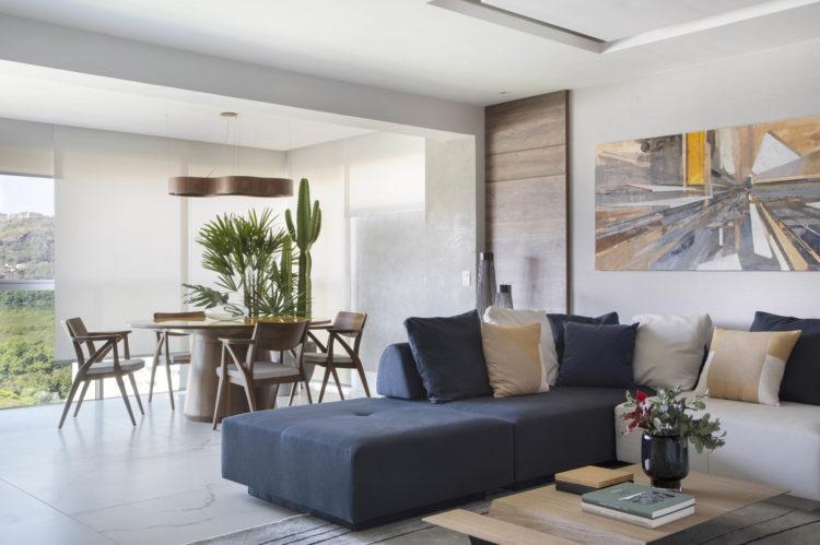 Com a saída de casa dos filhos, casal decidiu reformar o apartamento para aproveitar a nova fase da vida. Sala om sofá azul, varanda fechada com vidro e mesa redonda