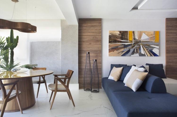 Sofá azul que da para os dois ambientes da sala, mesa redonda com tampo amarelo