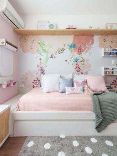 Quarto de menina com papel de parede florido atras .