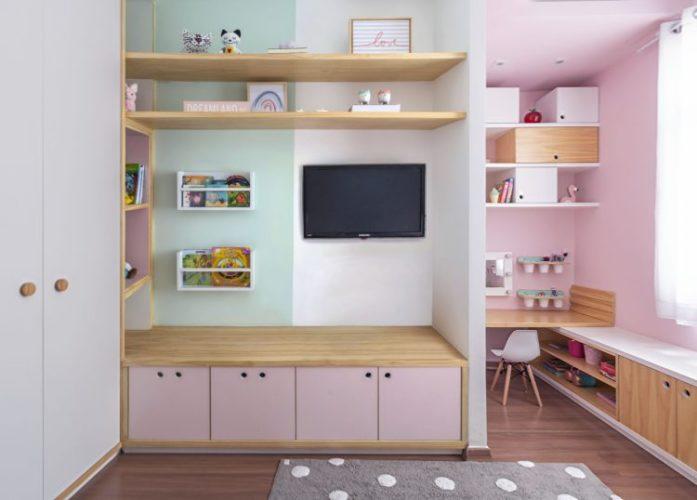 Quarto de menina decorado. Parede com tv instalada, embaixo armario baixo com prateleira me madeira e postas em rosa