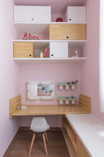 Cantinho de estudo no quarto de menina decorado. Entre paredes, uma bancada em madeira, e nichos brancos em cima