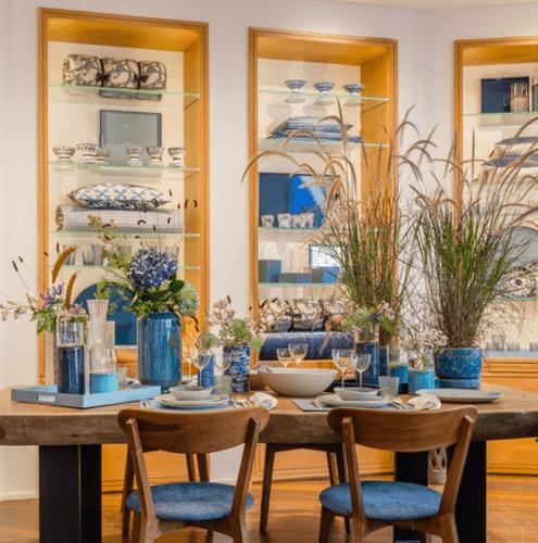 """Loja da Compagnie Française de l""""Orient e de la Chine no Boulevard Raspail - Paris. Mesa em madeira posta com louça e vasos azuis."""