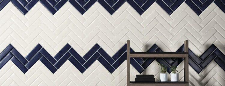 parede em cima da bancada de cozinha com revestimento azul e branco instalado na paginação espinha de peixe, na diagonal, intercalando as cores formado faixas