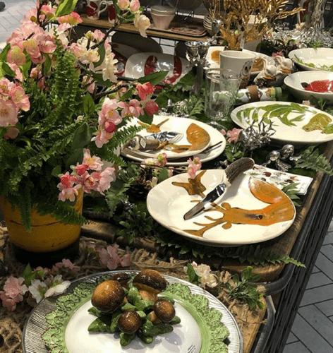 Mesa posta na loja francesa Au Bain Marie. Pratos com estampa de um alçe pintado e flores enfeitando a mesa