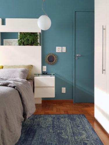 Parede de fundo do quarto, pintada de azul petróleo, inclusive a porta de entrada, que fica camuflada pintada da mesmo cor que a parede