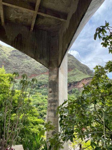 Uma foto de um pilar alto em cimento com montanhas ao fundo. Casa Pouso Alto em BH