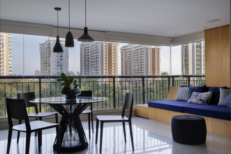 Varanda fechada com cortina de vidro, mesa redonda e sofá em um estrutura rigida em madeira com almofadas azuis