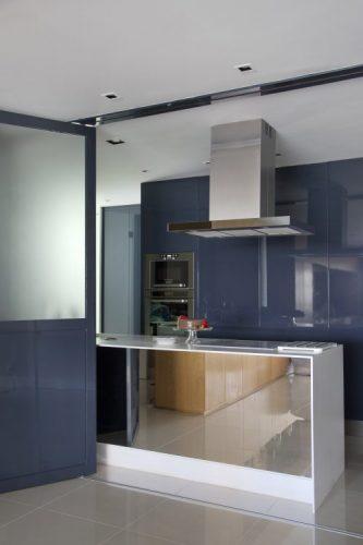 Apartamento na Barra repaginado via Miami. Cozinha integrada a sala. armarios azuis, bancada em ilha com coifa em cima