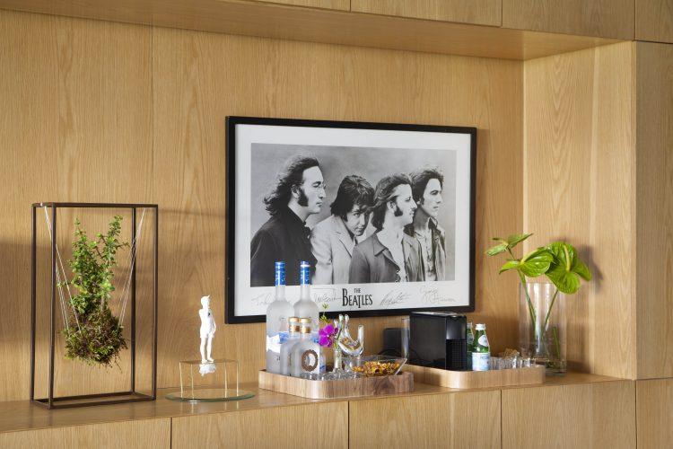 Nicho em madeira no móvel também em madeira clara. Bandeja com copos e uma foto dos Beatles
