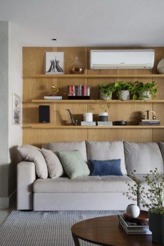 Sofá bege e a parede revestida em madeira com prateleiras, com livros e plantas