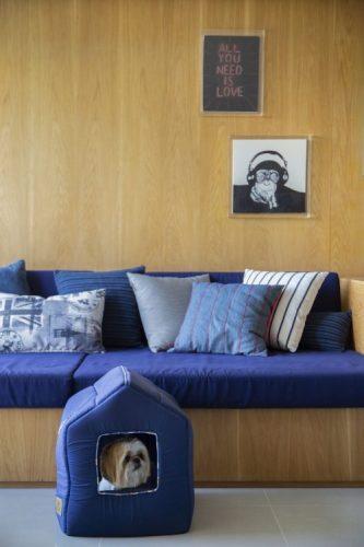 Apartamento na Barra repaginado via Miami, um cachorro shitzu dentro de uma casinha almofadada azul