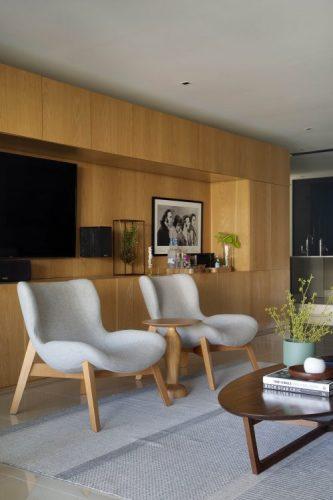 Parede longa com móvel em madeira clara,no meio um nicho vazado para a tv