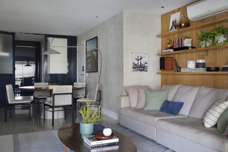 Apartamento na Barra repaginado via Miami, sala com sofá bege, atrás parede revestida em madeira e prateleiras. aoa fundo mesa redonda e parede em cimento queimado