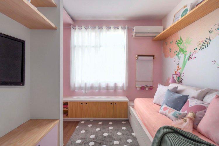 Quarto de menina decorado na cor rosa pintado nas paredes e atras da cama papel de parede florido