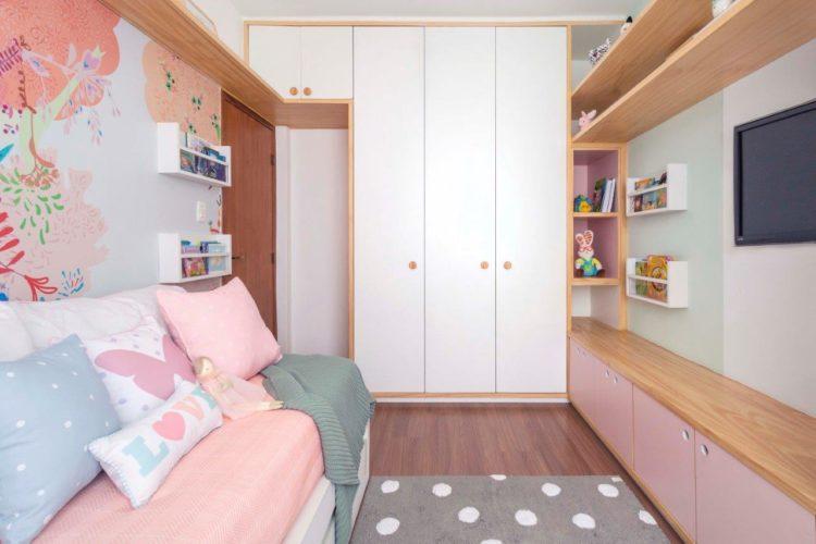 Boas soluções em um projeto de quarto de menina. Armarios com portas brancas, aramrio baixo embaico da tv com portas rosa e em frente cama com pape de parede florido atras.