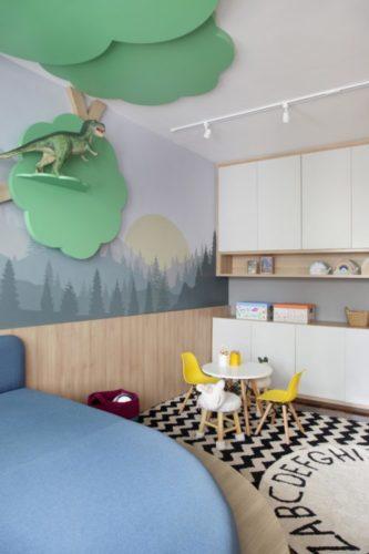 Brinquedoteca com uma arvore e madeira enfeitando, armarios fechados e mesa e cadeiras infantil