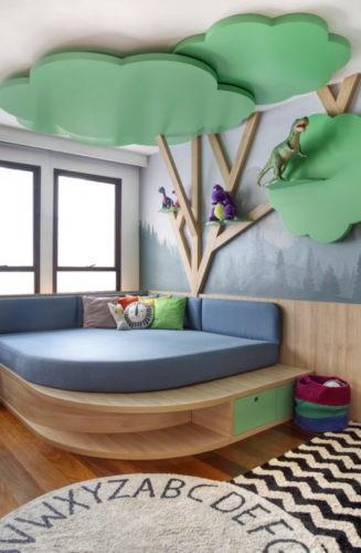 Rancho da família inspira brinquedoteca dos netos. Uma arvore em madeira instalada na parede, com galhos e copas sibindo pelo teto. Embaixo um futon azul
