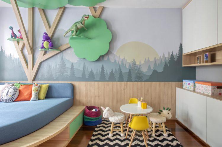 Rancho da família inspira brinquedoteca dos netos. Papel de paede de floresta, meia parede com lambri em madeira e uma arvore tb em madeira instalada na parede.