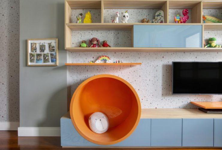 Rancho da família inspira brinquedoteca dos netos. Estante com um circulo laranja, rack baixo com portas azuis e nichos superiores em madeira.