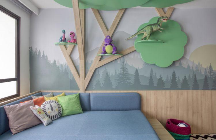 Uma arvore feita em madeira, com galhos e copas subindo pela parede. Prateleiras com bichos em pelucia