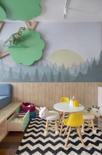 Espaço para crianças, com mesa e cadeiras infantis. papel de parede com floresta ao fundo.
