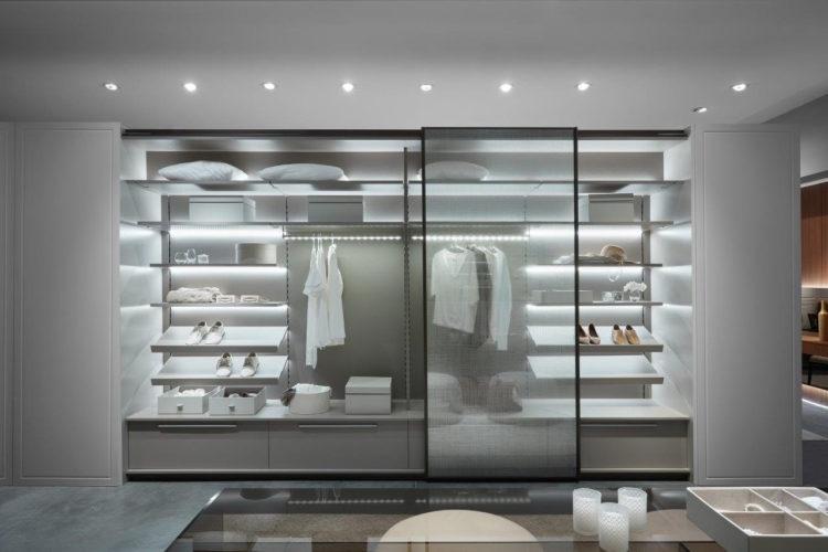 Armario em um closet com portas transparentes em vidro, prateleras brancas iluminadas