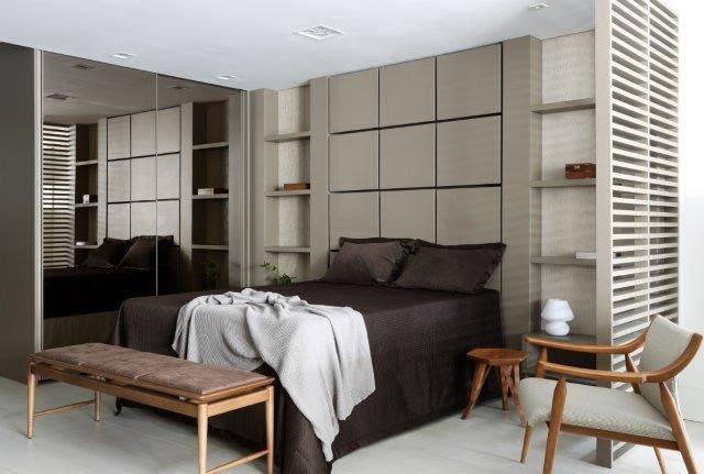 Cama de casal com lençol marrom, atrás da cama paienl em madeira com desenhos de quadrados na cor cinza