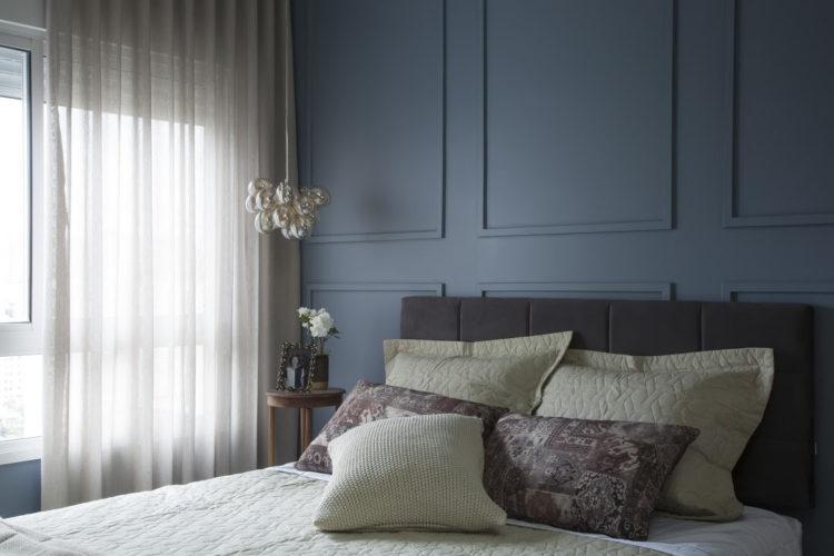 Boiserie: 5 dicas de arquitetos para usar esse elemento no décor, Quarto de casal com a parede atras da cama pintada de azul e com boiserie ( molduras finas) na mesma cor aplicada.