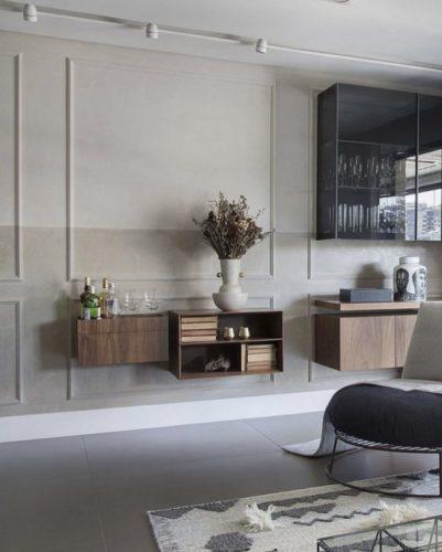 Sala com cores claras, boiseria aplicada na parede pintada em duas cores de tons de bege