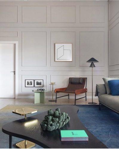 Sala decorada em estilo vintage, com pé direito alto e as paredes com aplicações de boiserie