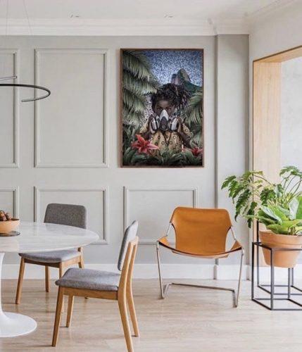 Sala de jantar, com a parede cinza e boiserie aplicada, um quadro pendura no mesmo tamanho dos quadrodos .