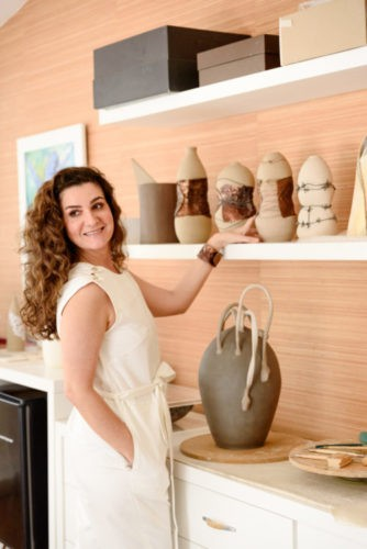 Foto da artista plástica Patricia Guereiro, vestida com um vestido bege e colocando a mão nas suas cerâmicas
