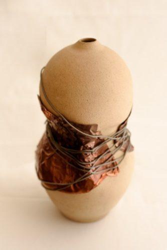 Vaso de cerâmica com um arame no meio para fazer alusõa ao crpo feminino usando espartilho.