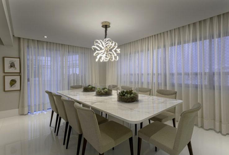 Projeto de cobertura em Salvador inspira criação de aplicativo Decor.App. Sala de jantar decorada em tons claros, duas janelas com cortinas plissadas em linho branco, mesa de jantar em marmore branco, cadeiras em tecido branco e piso em porcelano branco