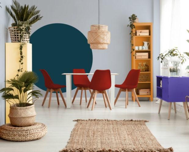 Sala de jantar com a parede de fundo pintada de azul clarinho, um circulo azul escuro no meio e cadeiras vermelhas na mesa branca